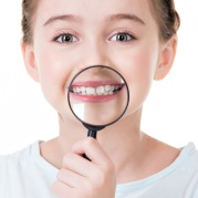 Close-up portrait of little girl showing teeth through a magnifying glass